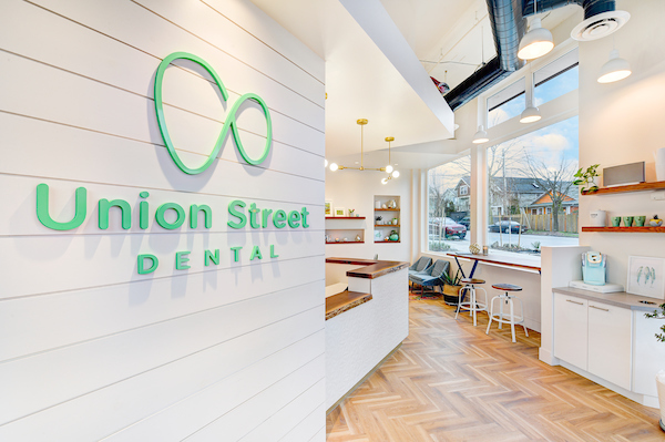 Walnut topped reception desk in window walled family dental in Madrona